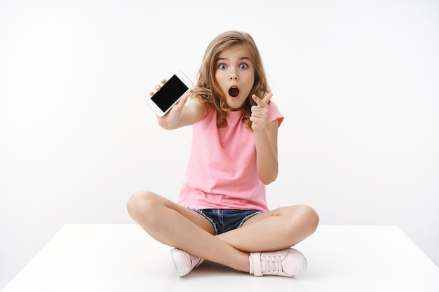 Verbaasd opgewonden europees blond tienermeisje in een hinderlaag gelokt, zit gekruiste benen, schudt smartphone met aanwijsscherm van mobiele telefoon, open mond verwonderd en onder de indruk, deel cool geweldig spel