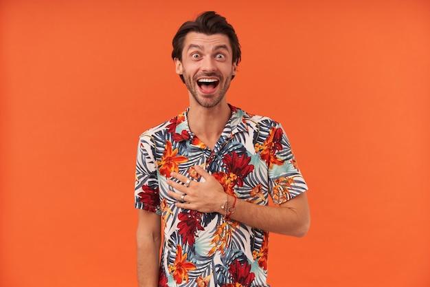 Verbaasd opgewonden jongeman met stoppels in kleurrijk overhemd houdt hand op de borst nabij het hart en kijkt verbaasd