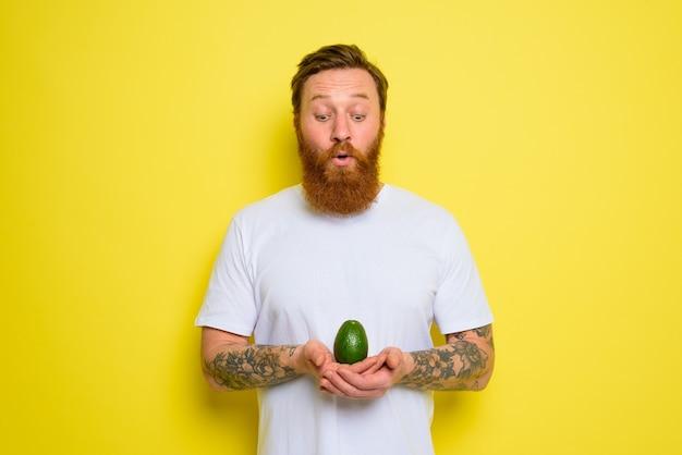 Verbaasd over baard en tatoeages houdt een avocado vast