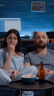 Verbaasd paar kijken naar film op tv 's nachts en eten popcorn