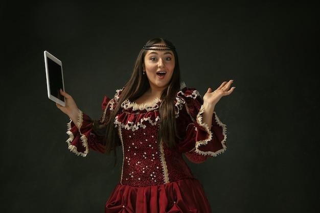 Verbaasd. portret van middeleeuwse jonge vrouw in rode vintage kleding met behulp van tablet op donkere achtergrond. vrouwelijk model als hertogin, koninklijk persoon. concept vergelijking van tijdperken, modern, mode, schoonheid.