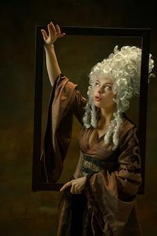 Verbaasd. portret van middeleeuwse jonge vrouw in vintage kleding met houten frame op donkere achtergrond. vrouwelijk model als hertogin, koninklijk persoon. concept vergelijking van tijdperken, modern, mode, schoonheid.