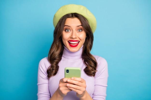 Verbaasd positief funky meisje gebruik smartphone sociale media lezen nieuws onder de indruk schreeuw wow omg draag meisjesachtige stijl trendy violet outfit hoofddeksels geïsoleerd over blauwe kleur muur