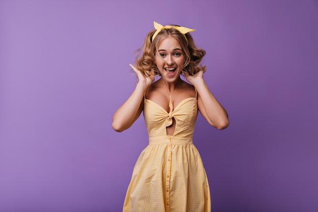 Verbaasd romantisch meisje dat op paars springt. portret van geïnspireerde dame in gele jurk die in de vrije tijd voor de gek houdt.