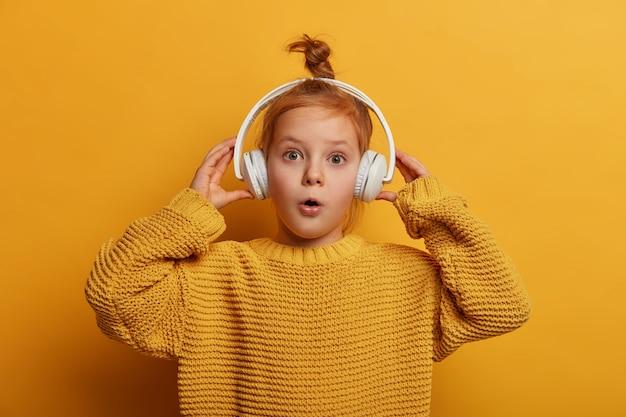 Verbaasd roodharige kind luistert naar audiotrack in koptelefoon, onder de indruk van hard geluid, opent zijn mond met verwondering, draagt een oversized gebreide trui, geïsoleerd op een gele muur. kinderen en hobby-concept