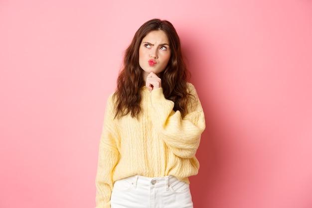 Verbaasd schattig meisje denken, kin aanraken en nadenkend fronsend, opzij kijkend naar logobanner met peinzend gezicht, staande over roze muur.