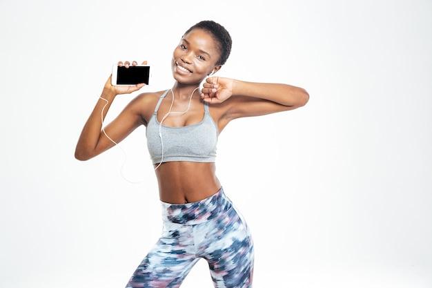 Verbaasd schattige jonge afro-amerikaanse sportvrouw luisteren naar muziek op mobiele telefoon