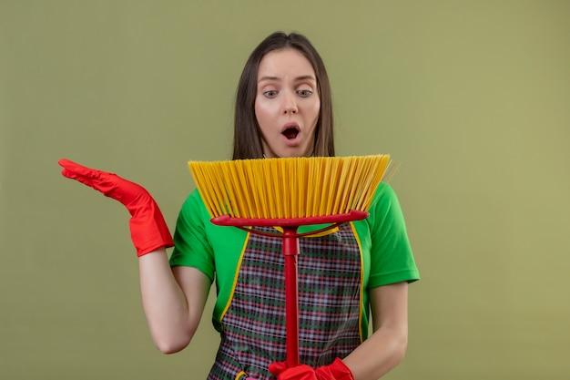 Verbaasd schoonmakend jong meisje die uniform in rode handschoenen dragen die dweil op haar hand op geïsoleerde groene achtergrond bekijken