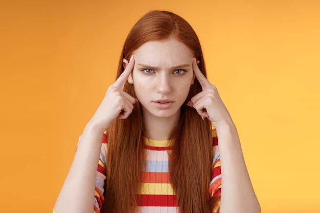Verbaasd serieus uitziende gestresste jonge vermoeide vrouwelijke student fronsend kijken ongelukkig aanraken tempels denken proberen focus, concentreren aandacht lezing onthouden hometask, oranje achtergrond