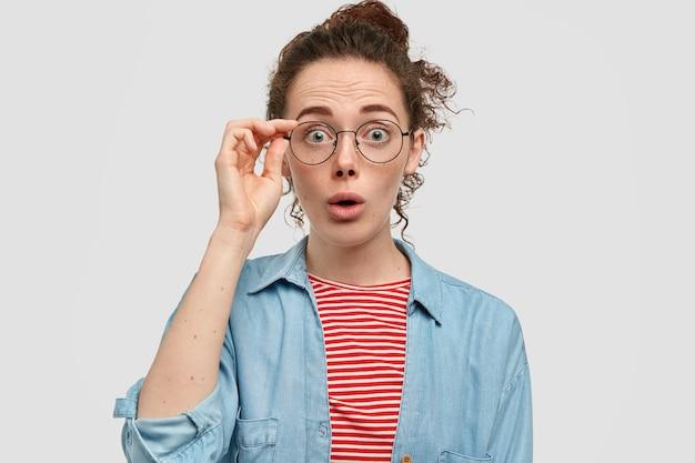 Verbaasd sproeterig meisje kijkt verbijsterd naar de camera, reageert op onverwacht nieuws
