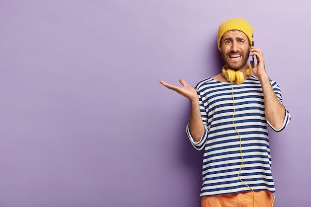 Verbaasd stijlvolle man poseren met zijn telefoon