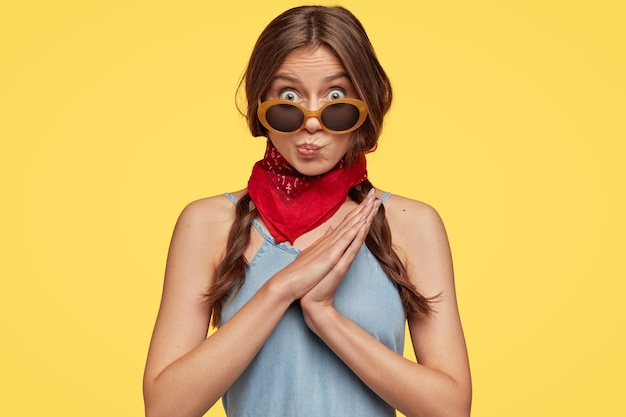 Verbaasd stomverbaasd tienermeisje heeft donker haar, gekamd in twee vlechten, portemonnees lippen, draagt modieuze tinten, rode bandana