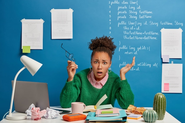 Verbaasd verontwaardigde kantoormedewerker voelt zich verward met operationele softwareproblemen, kijkt in paniek, schrikt van gegevensverlies, maakt aantekeningen in notitieblok, steekt beide handen op