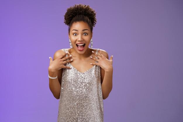 Verbaasd verrast aantrekkelijke afro-amerikaanse jonge vrouw in glinsterende avondjurk schreeuwen geluk wijzend zichzelf geamuseerd kan niet geloven dat lucky win casino loterij, blauwe achtergrond.
