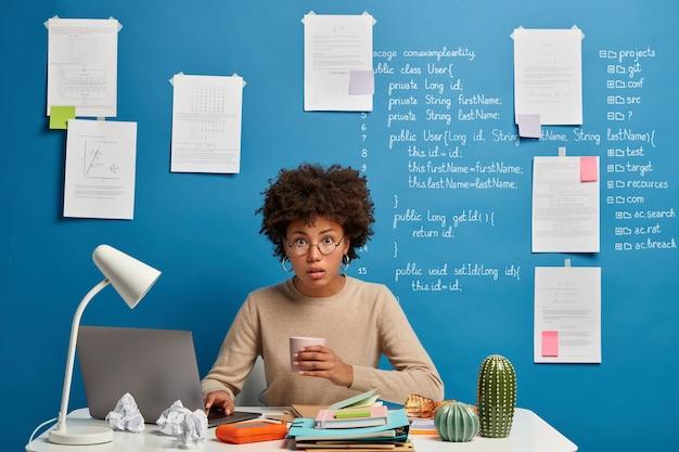 Verbaasd verrast computeranalist heeft koffiepauze, leest gepubliceerd op webpagina, draagt een ronde bril, poseert op bureaublad tegen blauwe muur met schriftelijke informatie