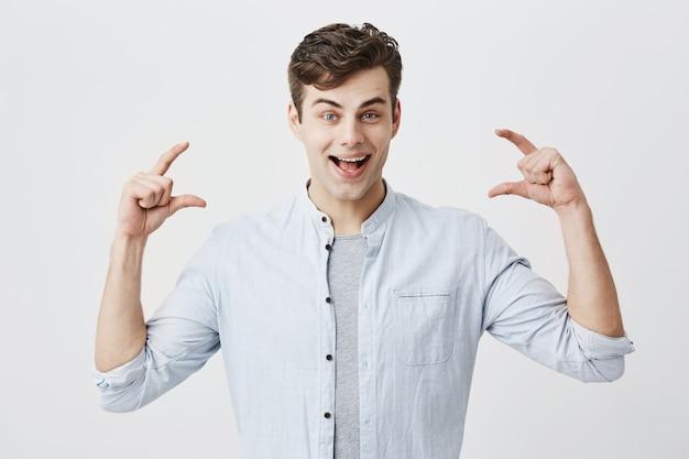 Verbaasd verrast europees jong mannelijk model dat met een glimlach met open mond vrolijk lacht, de grootte met beide handen van iets kleins in omvang demonstrerend, actief gebarend. lichaamstaal en gebaren.
