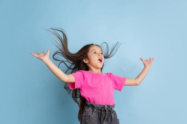 Verbaasd, vliegend haar. het portret van het kaukasische meisje op blauwe muur. mooi vrouwelijk model in roze overhemd. concept van menselijke emoties, gezichtsuitdrukking, jeugd, jeugd.