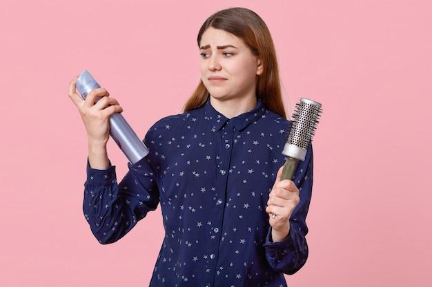 Verbaasd vrouwelijk model houdt haarlak en kam, kijkt verontwaardigd, gekleed in blauw overhemd, poseert op roze. europese vrouw wil nieuw kapsel maken.