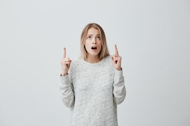 Verbaasd vrouwtje met blond geverfd haar, in trui die naar boven kijkt en wijst met haar vingers verrast om iets te zien. betrokken opgewonden jonge vrouw met wijd geopende mond