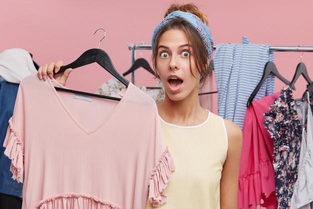 Verbaasd vrouwtje met wijd geopende mond, met hanger met roze jurk, verrast door de hoge prijs. vrouw in garderobe wordt geschokt met iets terwijl het kiezen van nieuwe outfit voor bruiloft
