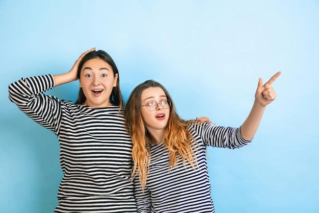 Verbaasd wijzen. jonge emotionele vrouwen geïsoleerd op gradiënt blauwe studio achtergrond. concept van menselijke emoties, gezichtsuitdrukking, vriendschap, advertentie. mooie kaukasische modellen in vrijetijdskleding.