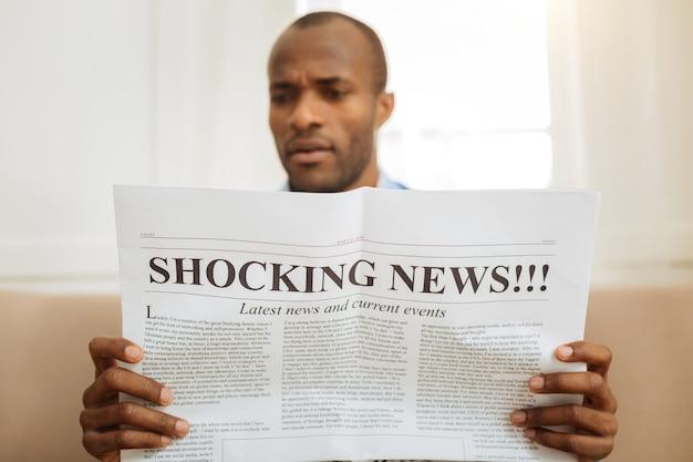 Verbaasd zijn. ernstige verbaasde afro-amerikaanse man die een krant vasthoudt en schokkend nieuws leest terwijl hij op de bank zit