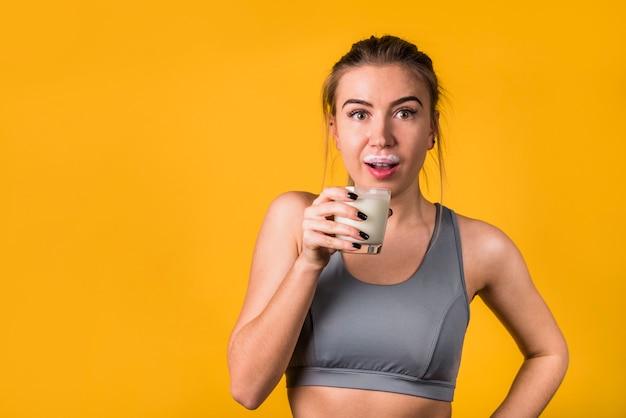 Verbaasde aantrekkelijke jonge vrouw in sportkleding met een glas melk