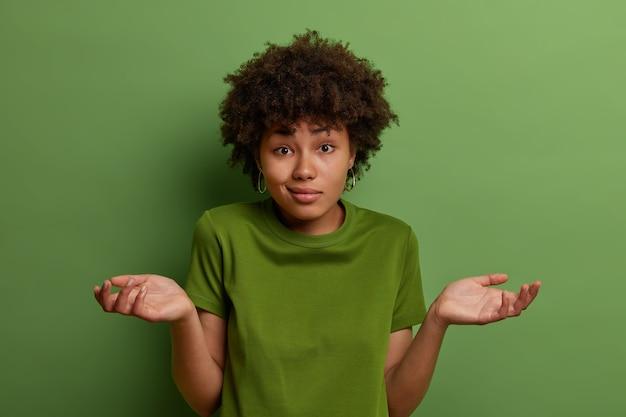 Verbaasde aarzelende jonge afro-amerikaanse vrouw spreidt handpalmen, voelt zich onzeker, kijkt verbijsterd, staat in vraag, draagt groen casual t-shirt in één kleur met achtergrond, neemt moeilijke beslissing