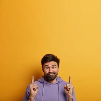 Verbaasde aarzelende man met baard, drukt lippen op, draagt paarse hoodie, wijst wijsvinger naar boven, aarzelt wat te kopen, heeft geen idee van uitdrukking, geïsoleerd op gele muur, lege ruimte naar boven