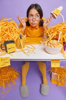 Verbaasde aarzelende studente zit aan rommelig bureau haalt schouders op heeft ontevreden uitdrukking draagt ronde bril geel shirt huispantoffels heeft deadline omringd door veel gesneden papier