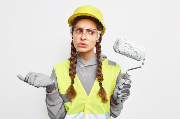 Verbaasde aarzelende vrouw bouwer of decorateur