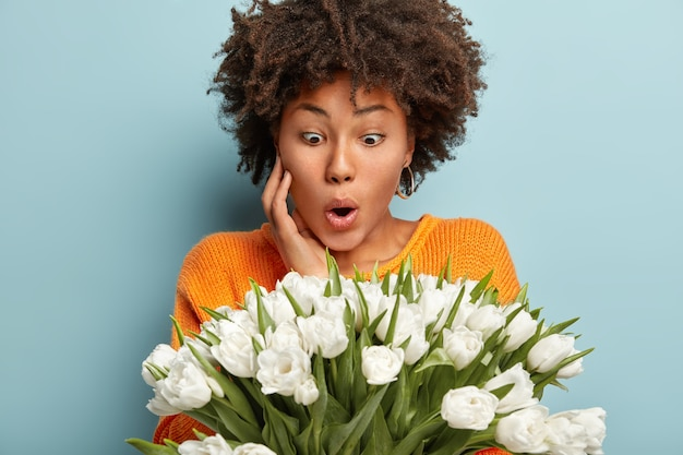 Verbaasde afro-amerikaanse dame staart naar witte prachtige bloemen, kan ogen niet geloven, houdt de hand op de wang, draagt een oranje trui, geïsoleerd over blauwe muur. mensen en onverwacht reactieconcept