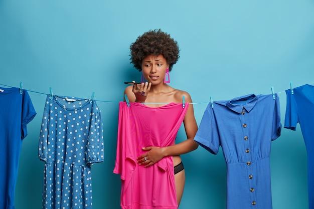 Verbaasde afro-amerikaanse vrouw belt, vraagt om advies wat ze moet dragen, te laat zijn op de date, wacht tot kleren drogen na het wassen, staat uitgekleed, verstopt zich achter roze jurk geïsoleerd op blauw
