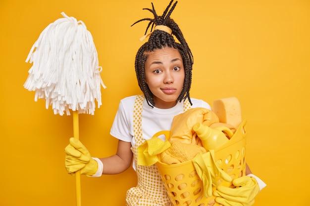 Verbaasde afro-amerikaanse vrouw met dreadlocks heeft huishoudelijke taak
