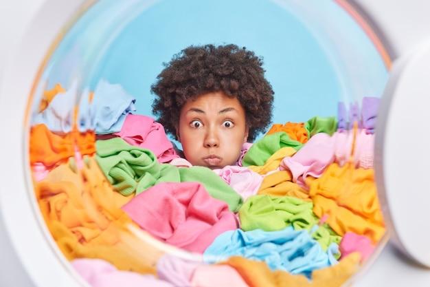 Verbaasde afro-amerikaanse vrouw met krullend haar blaast wangen maakt grappige grimas verdronken in veelkleurige washoudingen van binnenuit van wasmachine kan haar ogen niet geloven
