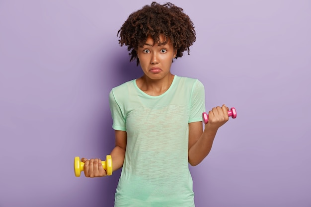 Verbaasde afro-amerikaanse vrouw ziet er verrassend uit, houdt twee halters vast, werkt aan spieren, draagt t-shirt, houdt van fitness en sport, geïsoleerd op paarse muur. dame met gewichten traint in de sportschool