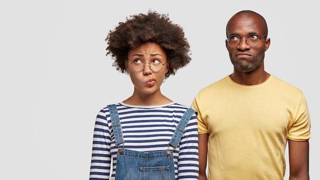 Verbaasde afro-amerikaanse zus en broer buigen hun lippen en kijken aarzelend ergens opzij