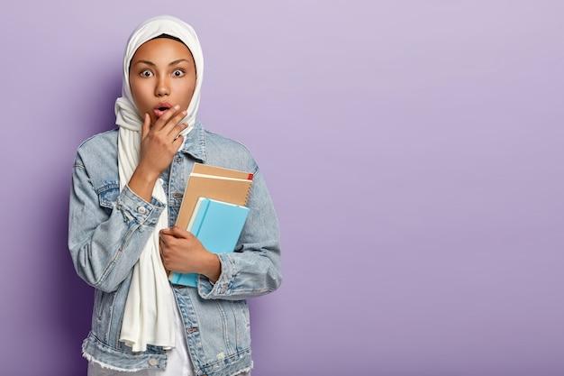 Verbaasde arabische student gaat naar de middelbare school, heeft een donkere huid, draagt een notitieblok om aantekeningen te maken, draagt een witte sluier over het hoofd, heeft eigen religieuze tradities, poseert binnen