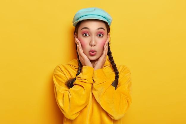 Verbaasde aziatische dame houdt lippen rond, kijkt verrast, reageert op roddels, draagt stijlvolle hoed en corduroy geel sweatshirt