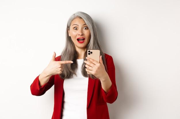 Verbaasde aziatische dame in rode blazer wijzende vinger naar smartphone, staren onder de indruk naar camera, iets online, witte achtergrond tonen.