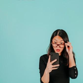 Verbaasde aziatische vrouw die smartphone bekijkt