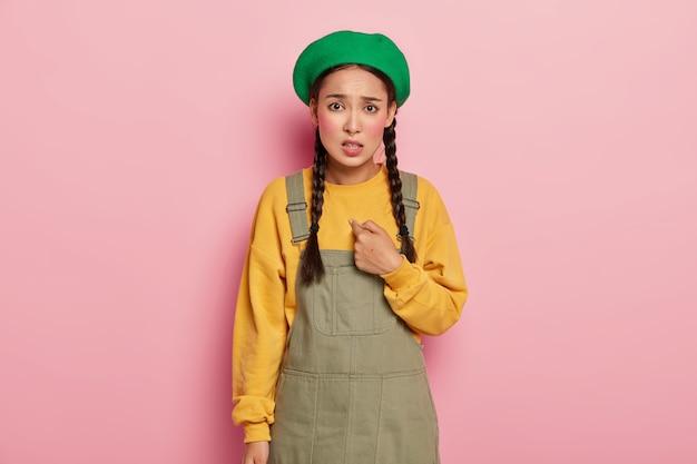 Verbaasde aziatische vrouw wijst naar zichzelf, wordt geselecteerd, vraagt waarom ik, kijkt met een onaangename gezichtsuitdrukking, draagt groene baret