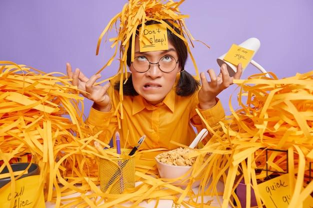 Verbaasde aziatische vrouwelijke kantoormedewerker probeert niet te slapen heeft deadline maakt zich zorgen expressie werkt lange uren draagt ronde bril casual shirt gesneden papier rond