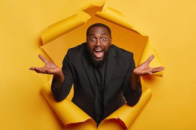 Verbaasde, bebaarde afro-man spreidt zijn handpalmen, voelt aarzelend en onbewust, doet geen idee wat er is gebeurd, draagt een formeel zwart pak, poseert in een gescheurd geel papieren gat binnen