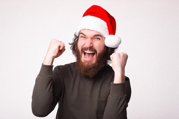Verbaasde bebaarde hipster man wachtend op het nieuwe jaar 2021 schreeuwen en vieren