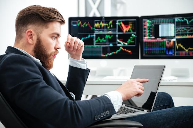 Verbaasde bebaarde jonge zakenman die laptop gebruikt en erop wijst in kantoor