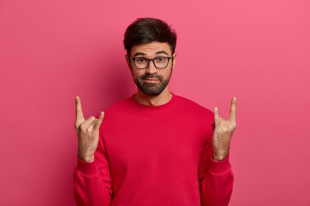 Verbaasde, bebaarde man bezoekt geweldig muziekfestival, maakt rock-'n-roll-gebaar, luistert naar zijn favoriete zware vleeslied, kleedt zich nonchalant aan, poseert tegen een roze muur. rock leeft voor altijd