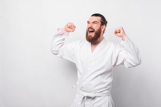 Verbaasde bebaarde man in taekwondo-uniform vieren over witte muur
