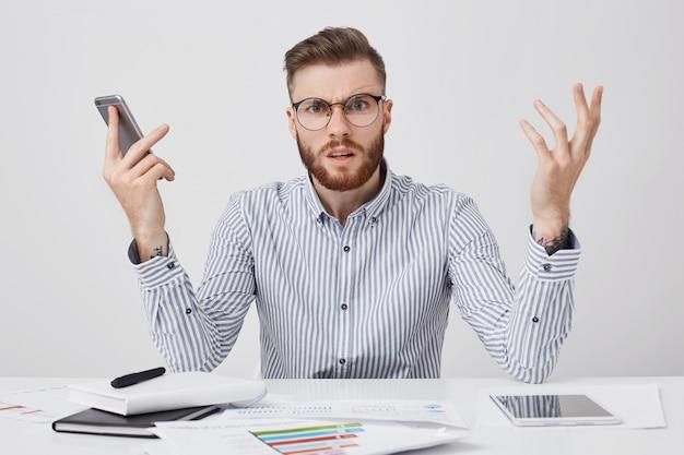 Verbaasde bebaarde man met verontwaardigde blik kan niet begrijpen waarom er geen antwoord is van een collega