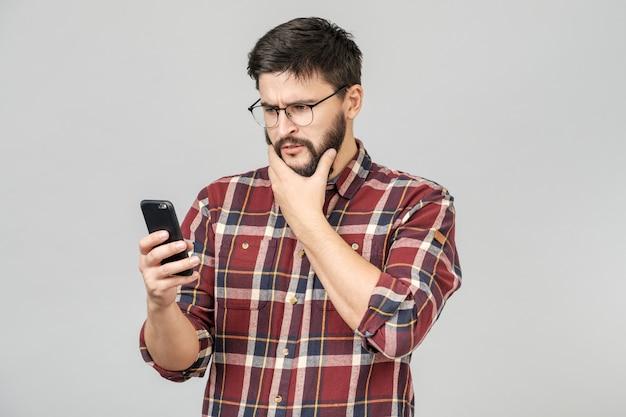 Verbaasde bebaarde man met verwarring die schokkend nieuws leest